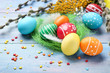 Colorful easter eggs with feathers and sprinkles on blue wooden table