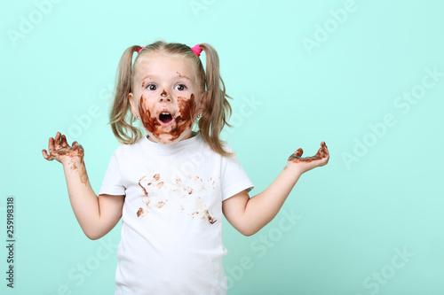 Leinwandbild Motiv Happy little girl in chocolate on mint background