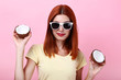 Young redhaired woman with coconuts on pink background