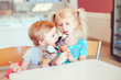 Leinwanddruck Bild - Lifestyle portrait of two happy Caucasian cute adorable funny children girls sitting together sharing ice-cream. Love sisters friendship concept. Best friends relatioships. Tasty summer food
