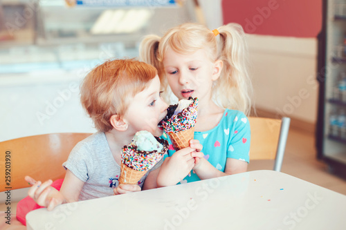 Leinwanddruck Bild Lifestyle portrait of two happy Caucasian cute adorable funny children girls sitting together sharing ice-cream. Love sisters friendship concept. Best friends relatioships. Tasty summer food
