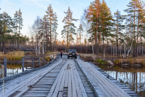 SUV moves on a wooden bridge over a river in the forest