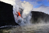 Hot lava flows from high cliff into the ocean in Big Island in Hawaii