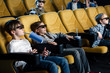 friends in 3d glasses watching movie in cinema and holding paper cups