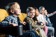 selective focus of smiling cheerful multicultural friends watching movie in cinema together
