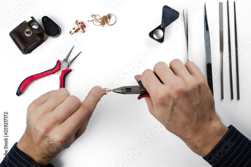 Repair of gold jewelry. Hands of the jeweler with tools and jewellery isolated on white background. © vladk213