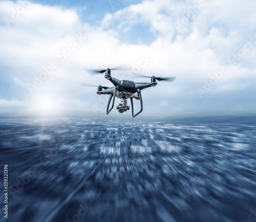 Leinwandbild Motiv Modern dark drone in flight over the city.