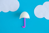 White egg and drinking straw in form of umbrella with origami clouds abstract. - 259232333