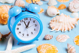 Blue sea background with alarm clocks and seashells, summer holiday and vacation time concept - 259248352