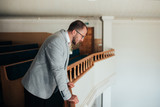 Wedding photo of emotions of a bearded groom with glasses in a gray jacket in the church building
