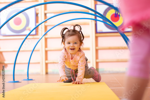 Leinwandbild Motiv Baby girl crawling on mat in gym class. Lifestyle concept of children activity.