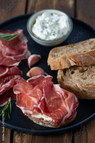 Leinwandbild Motiv coppa di parma meat, cream cheese and ciabatta bread on wooden surface