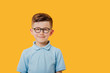 portrait of a beautiful and handsome little boy who looks into the camera and smiles, in glasses, dressed in blue shirt, isolated on yellow background, copy space