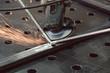Leinwandbild Motiv Worker in metal factory grinding workpiece with sparks flying