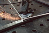 Worker in metal factory grinding workpiece with sparks flying