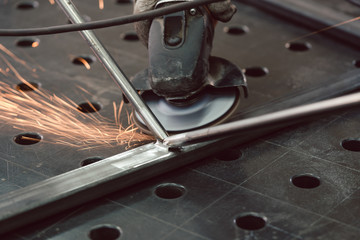 Worker in metal factory grinding workpiece with sparks flying © Kzenon