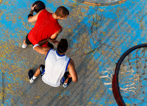 Fototapeten Basketball Top view of two young friends playing basketball on court outdoors.