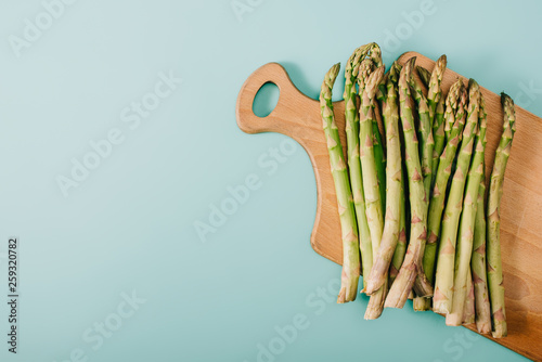 top view of green raw asparagus on wooden cutting board on blue background - 259320782