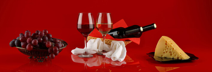 Panorama with glasses of wine, cheese and grapes on a red background © parsadanov