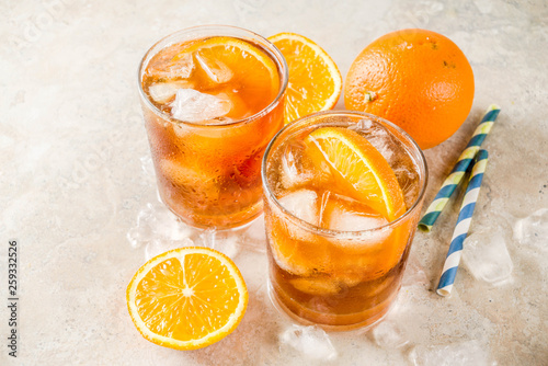 Cold summer cocktail, Iced coffee dink with orange slices, stone table copy space