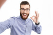 Leinwandbild Motiv Happy bearded elegant man in eyeglasses making selfie