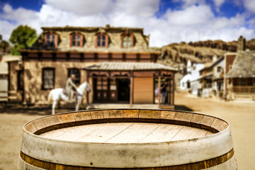 Wooden old table of free space for your decoration and wild west blurred background of big building and cowboy on horse.