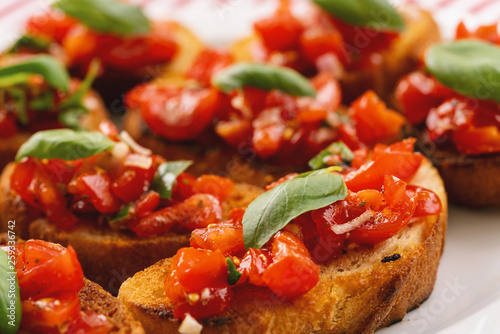 Tasty savory tomato Italian appetizers, or bruschetta, on slices of toasted baguette garnished with basil, close up - 259336742