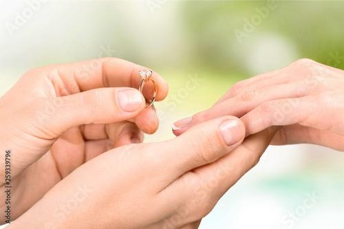 Leinwandbild Motiv Close up Groom Putting the Wedding Ring on bride