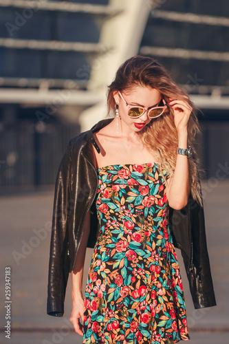 fototapeta na ścianę beautiful sexy woman in a short skirt walking in the city in Sunglasses