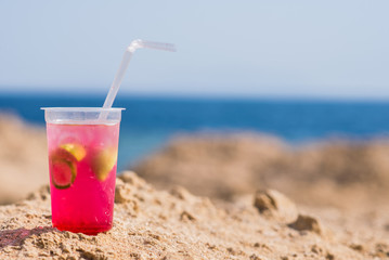 Bright cocktail placed on a sunny summer beach against the blue sea - Image