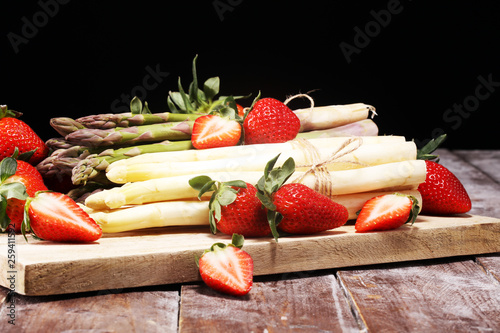 Leinwandbild Motiv White and green asparagus with strawberries on wood