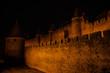 canvas print picture - Festung La Cité beleuchtet bei Nacht von der Seite, Carcassonne, Frankreich