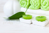 Green plant leaf, aromatic sea salt, candles, vase and towels. Concept for spa, beauty and health salons. Close up photo on white wooden background, selective focus