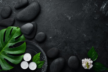 Zen stones and leaves with water drops. Spa background with spa accessories on a dark background. Top view. Free space for your text. © Yaruniv-Studio