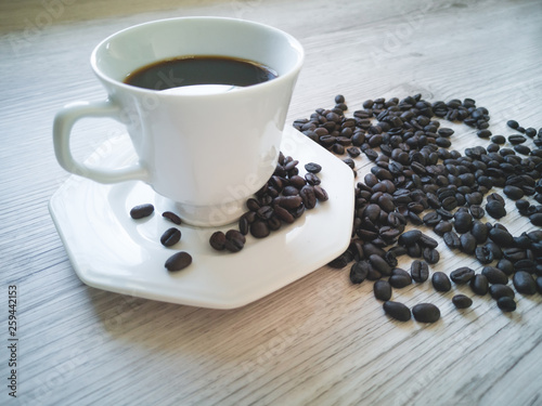 Coffee cup with coffee beans scattered on the table © Gustavo