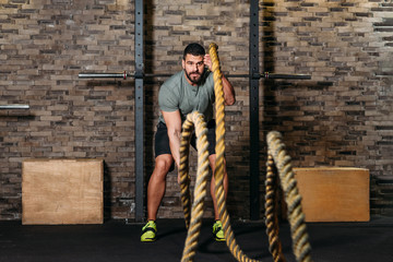 Athlete workout with battle rope at gym
