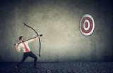business man trying to hit a target his goal with bow and arrow