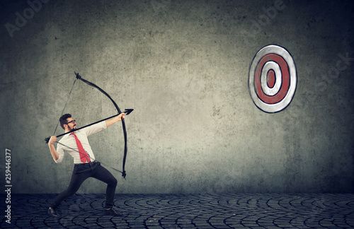 business man trying to hit a target his goal with bow and arrow - 259446377