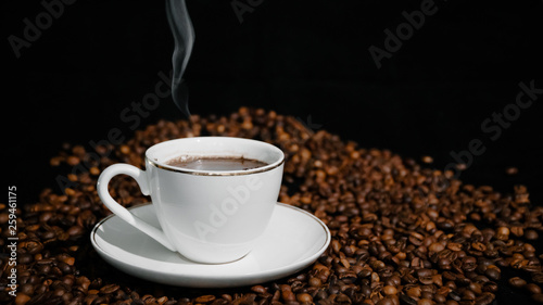 Cup with hot coffee and steam on a dark background