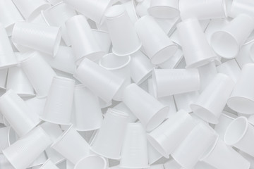 The texture of randomly scattered white disposable plastic cups. Abstract background of plastic dishes.