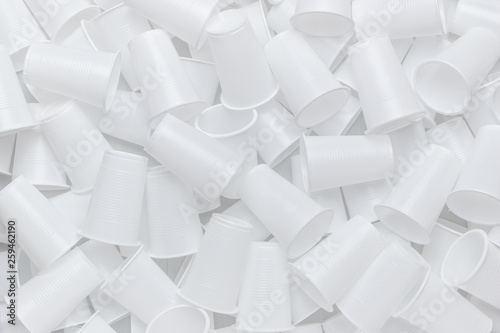 The texture of randomly scattered white disposable plastic cups. Abstract background of plastic dishes. - 259462190