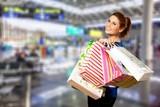 Młoda kobieta z torba na zakupy na zamazanym zakupy centrum handlowego tle