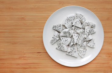 Fresh sliced dragon fruit on white plate against wooden board background.
