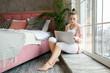 Leinwandbild Motiv Beautiful young woman with laptop resting at home
