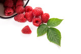 White cup with ripe raspberries and green leaf isolated on white background.