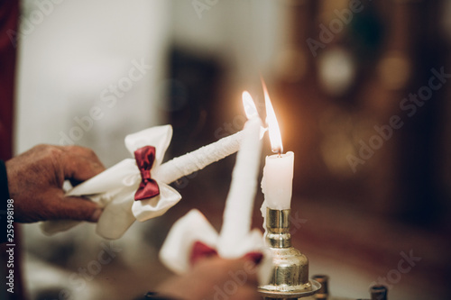 candle lighting up for bride and groom in church during wedding ceremony © sonyachny