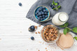 Granola muesli, milk and ripe blueberries with mint leaves, healthy breakfast concept, wooden background, top view