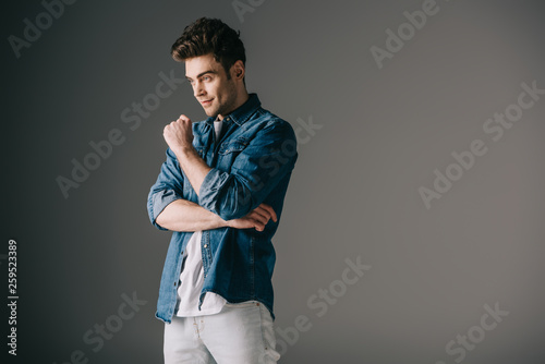 canvas print picture handsome man in denim shirt and jeans looking away on grey background
