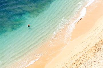 Hombre mayor dándose un baño en playa solitaria