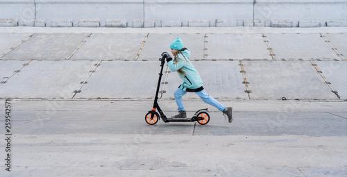 Leinwandbild Motiv Activities: A school girl with a blue jacket riding a scooter on a gray concrete promenade.